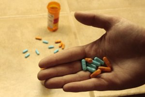 RENO, NV - An anonymous drug dealer holds a mix of Vyvanse(blue) and Adderall(orange) pills. This full time student at UNR sells only to people she knows well and can trust. Once these pills are sold her dealing days are over. She no longer refills her prescription because of health complications related to the pills. CREDIT: Nate Eng
